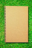 Brown cover notebook on green grass field. Blank notebook open two pages on green grass field stock photography