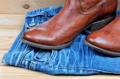 Brown cowboy boots on blue jeans. New classical leather brown cowboy boots on blue classical jeans royalty free stock photos