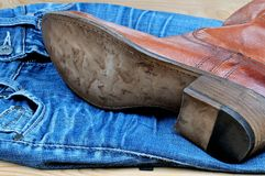 Brown cowboy boots on blue jeans. New classical leather brown cowboy boots on blue classical jeans stock photo