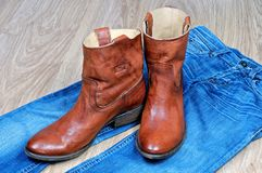 Brown cowboy boots on blue jeans. New classical leather brown cowboy boots on blue classical jeans royalty free stock photography