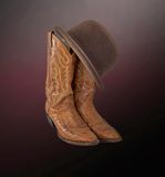 Brown cowboy boots and a brown derby Royalty Free Stock Images
