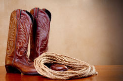 Brown cowboy boots and a coil of rope on brown Stock Photos