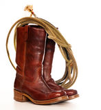 Brown cowboy boots and a Lasso. Vertical image of a pair of brown cowboy boots and a Lasso on a white background royalty free stock photo
