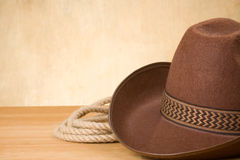 Brown cowboy hat and rope on wood Stock Photo