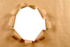 Brown craft paper background with untidy torn hole, white copy space Stock Photos