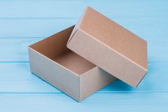 Brown craft paper box or carton. Close up. Blue wood background royalty free stock images