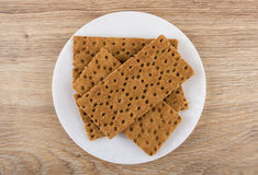 Brown crispbread in white plate on wooden table Royalty Free Stock Photos