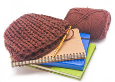 Brown crochet hat with golden hook, yarns and books. Royalty Free Stock Photo