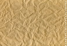 Brown crumpled old kraft paper with perforation, background royalty free stock image