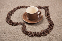 Brown cup of on burlap with coffee heart. Brown cup of on burlap with coffee beans heart Stock Image