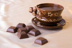 Brown cup and chocolate. A photo of brown clay cup and chocolate Stock Images
