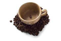 Brown cup with coffee beans around it Royalty Free Stock Photo