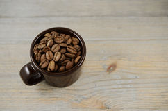 Brown cup with coffee beans Stock Images