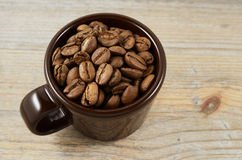 Brown cup with coffee beans Royalty Free Stock Photography