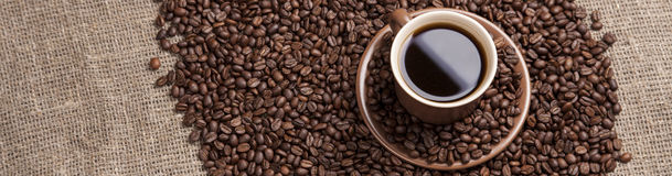 Brown cup with coffee on coffee beans. Brown cup with coffee on heap of coffee beans from top Stock Photography