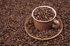 Brown cup with coffee on coffee beans. Brown cup with coffee on heap of coffee beans from top Stock Images