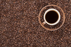 Brown cup with coffee on coffee beans. Brown cup with coffee on heap of coffee beans from top Stock Photo