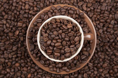 Brown cup with coffee on coffee beans. Brown cup with coffee on heap of coffee beans from top Royalty Free Stock Photo
