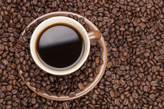 Brown cup with coffee on coffee beans from top. Brown cup with coffee on heap of coffee beans from top Stock Photo