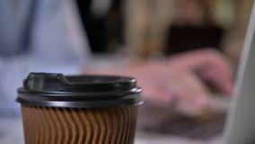 Brown cup of coffee on table in office, hands of businessman are typing on laptop on background, blurred background. Working concept stock footage