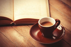 Brown cup of the coffee and vintage book. Photo with filter as a retro color image style Stock Photography