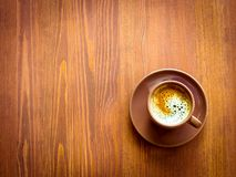 Brown cup of frothy coffee on wooden background Royalty Free Stock Photo