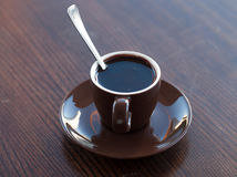 A brown cup of hot chocolate on a wooden table surface Royalty Free Stock Photos