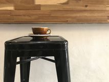 Brown cup of hot coffee with saucer on black metal bar stool. With natural wood coffee bar and white background in coffee shop stock photography
