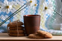 Brown cup and large biscuits with sesame, flax and sunflower seeds with flowers on wooden table stock photography
