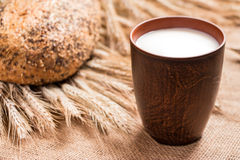 Brown cup of milk, a loaf of bread, wheat spikelets . Royalty Free Stock Photos