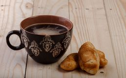 Brown Cup with ornaments filled with tea and two croissants on a light wooden background royalty free stock image