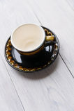 Brown cup and saucer. On wooden background Royalty Free Stock Images