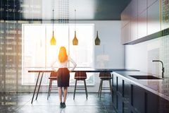 Brown cupboard kitchen interior with table, woman stock photography