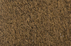 A BROWN CUSHION. OF BONDED DRIED GRASS TEXTURE AS BACKGROUND Royalty Free Stock Image