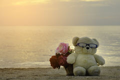 Brown cutie bear doll and flowers basket sit on  the beach floor Stock Image