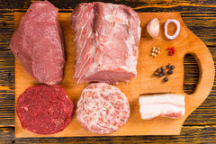 Brown cutting board with raw meat slices. Brown wooden cutting board with raw meat slices and samples of garlic, onion and hot pepper spice Stock Image