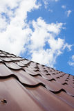 Brown-Dach der Metalldeckung auf dem Himmelhintergrund Stockfotografie