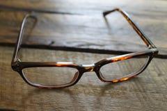 Brown-Damenmode-Brillen auf einem hölzernen Hintergrund lokalisiert Lizenzfreie Stockbilder