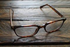 Brown-Damenmode-Brillen auf einem hölzernen Hintergrund lokalisiert Stockbild