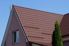 Brown deckte Dach auf einem Privathaus mit einem Fenster mit Ziegeln stockbilder