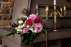 Brown decorative fireplace with flower arrangement and candles Stock Photos