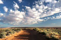 Brown Desert Road Between Green Leafed Plants Under Gray Cloudy Sky during Daytime Royalty Free Stock Images