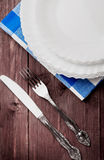 Brown Desk with a set of white plates and a knife with a fork Stock Image
