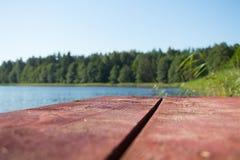 Brown deski jezioro most przeciw niebieskiemu niebu, woda, zieleni płochy i las i obraz royalty free