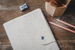 Brown diary cover with pencils and pencil sharpener on wooden ba Stock Photography