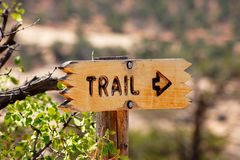 Brown directional sign for a trail pointing to the right. Wooden sign giving information about the direction of the path Royalty Free Stock Photography