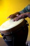 Brown Djembe con le mani su Bk giallo Fotografia Stock