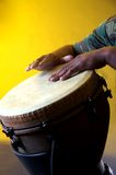 Brown Djembe With Hands On Yellow Bk. A brown Djembe with hands against a yellow background in the vertical format Stock Photography