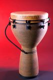 Brown Djembe Isolated On Red. A complete brown Djembe isolated against a red background in the vertical format Royalty Free Stock Photography