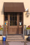 Brown door. With a brown awning and steps and railing Royalty Free Stock Photography